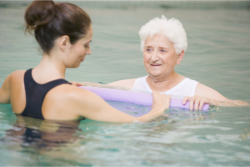 Physical therapist helping an elderly woman in physical strengthening on the pool.